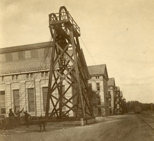 Historical sepia photo of the Telodyne wheel tower in front of a stone workshop building